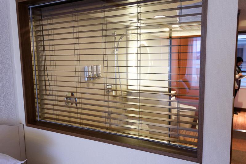 バスルームとベッドルームの間は窓で仕切られている。アメニティは充実している
