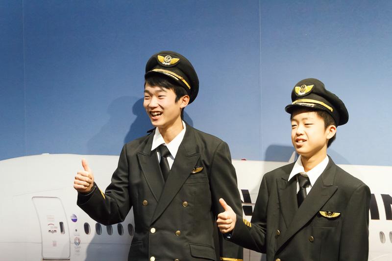 パイロットやCA(客室乗務員)の制服を着て記念撮影する参加者。前から袖に腕を通して後ろを面ファスナーで留めるだけなのですぐに着ることができる