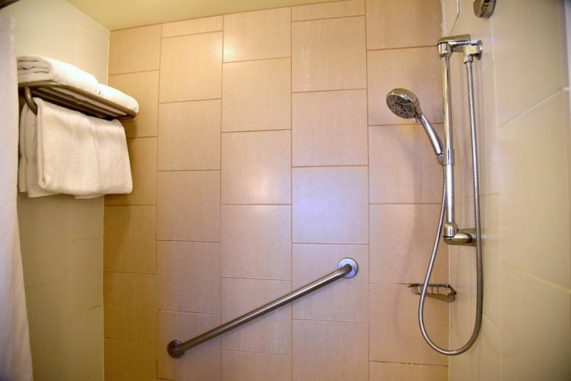足が伸ばせるサイズ感のバスタブ。シャワーは取っ手をひねってお湯を出すタイプ