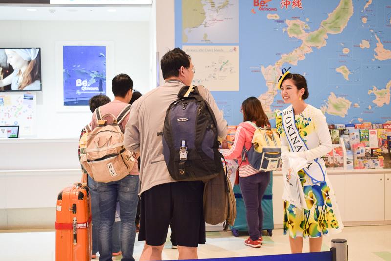 続々と降り立つ搭乗客をミス沖縄スカイブルーの嘉数晴花さんらが出迎える。嘉数晴花さんと記念撮影をする姿も見られた