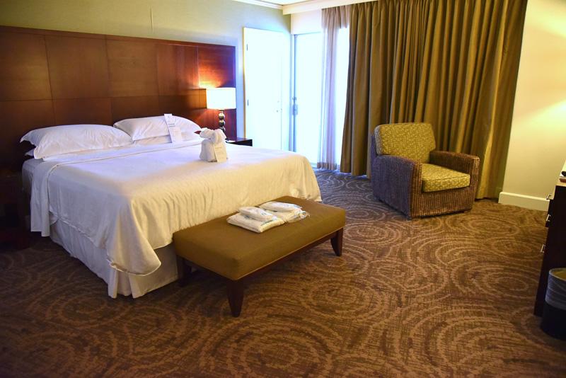 キングサイズベッドとともに、スイートルームのサービスとしてスリッパやガウンなども一緒に置かれている