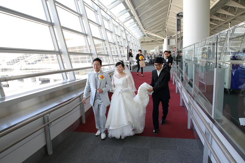 飛行機へ向かう通路を進む新郎新婦の姿も不思議な光景だ