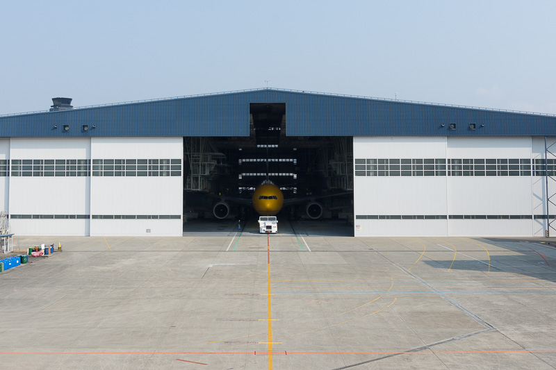 格納庫が開き、C-3PO ANA JETがトーイングカーで牽引されて青空の下に登場