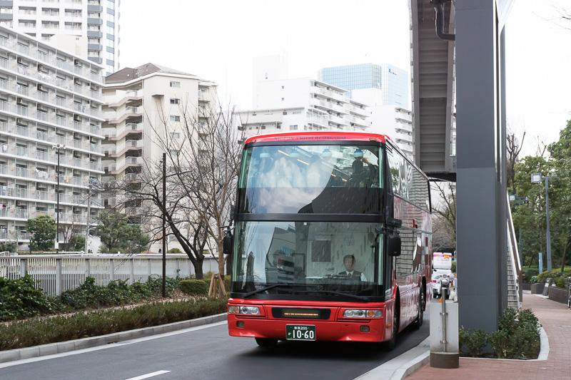 バス走行中のシーン。深紅のボディが目立つ