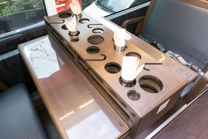 テーブル中央にグラス置き。2号車では日本酒用にお猪口と徳利が加わっている。細いS字はライングラスをホールドするもの