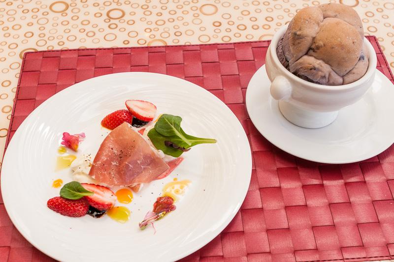 アペタイザーとしてテーブルに提供された「ストロベリーとパンチェッタのカプレーゼ」とカップに入ったパン
