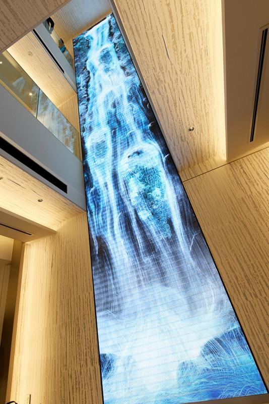 向かい側の壁には、同じく3フロア分の壁に巨大ディスプレイを貼り付け、滝の映像が流している。こちらは、パトリック氏の作品の植物を一部モチーフとして使いながら、チームラボがデジタル作品として制作したもの。時間帯や季節によって色合いが変化する