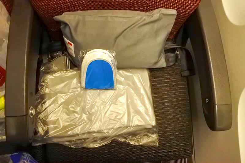 「新・間隔エコノミー(JAL SKY WIDER)」を採用したシート。座席には、枕、毛布、スリッパとともに鶴丸マーク入りのヘッドホンが用意されている