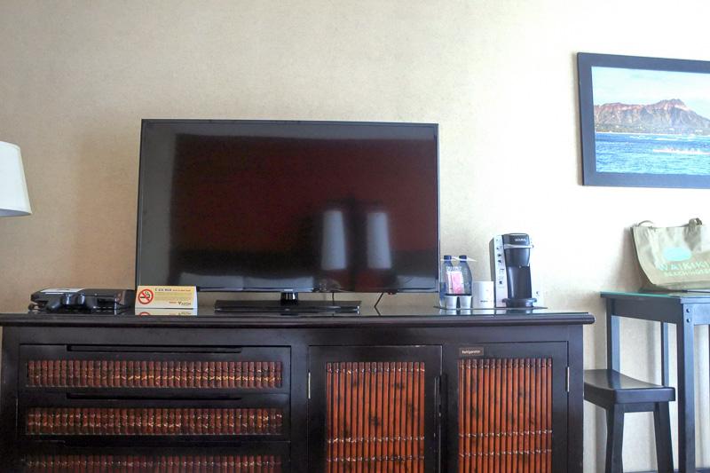 ベッドの目の前には大型の液晶テレビ。チェストの向かって右側に空の冷蔵庫とグラスなどが入っている