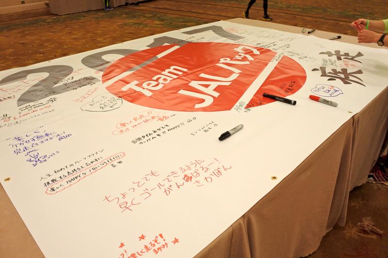 「Team ジャルパック」と「疾走」の文字が描かれたバナーへ意気込みを書き込む参加ランナーたち