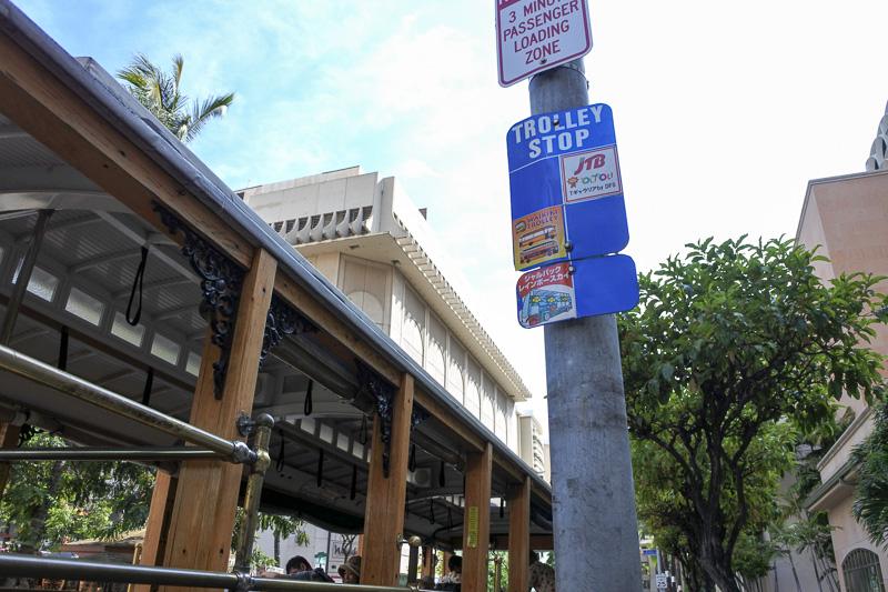 「Tギャラリア ハワイ by DFS」の建物外のバス停に「カイムキ・カハラルート」のトロリーが停車する