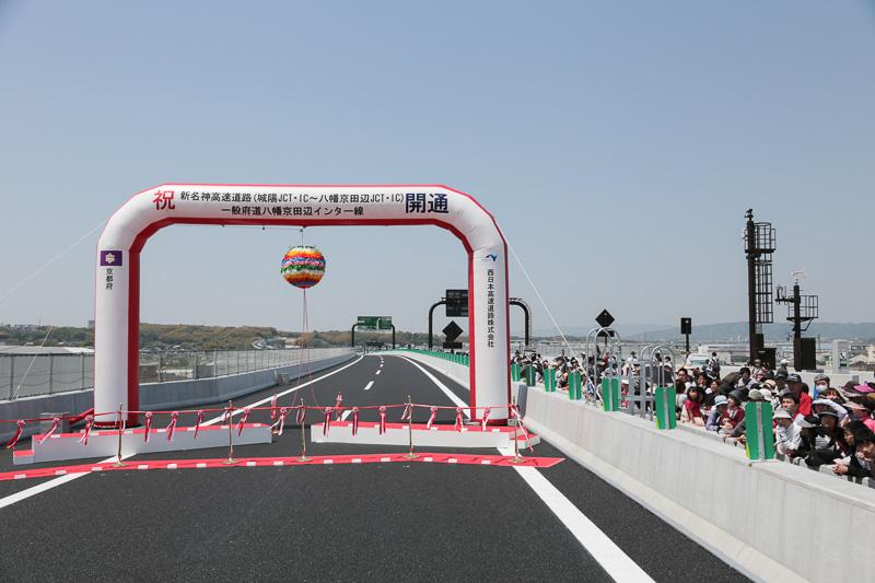 テープカットは、木津川橋の中央付近で行なわれた。写真向かって右の上り車線には、城陽市主催の「開通直前フリーウォーキング」参加者たちが集まっている