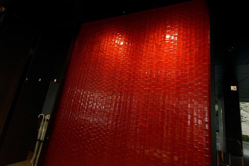 エントランスの自動扉は木製。赤い箔をまぶした独特の風合いで、重厚さを感じさせる