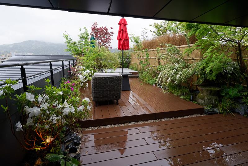 たっぷりの植栽と、ソファや畳敷きの月見台がある庭園に出られる