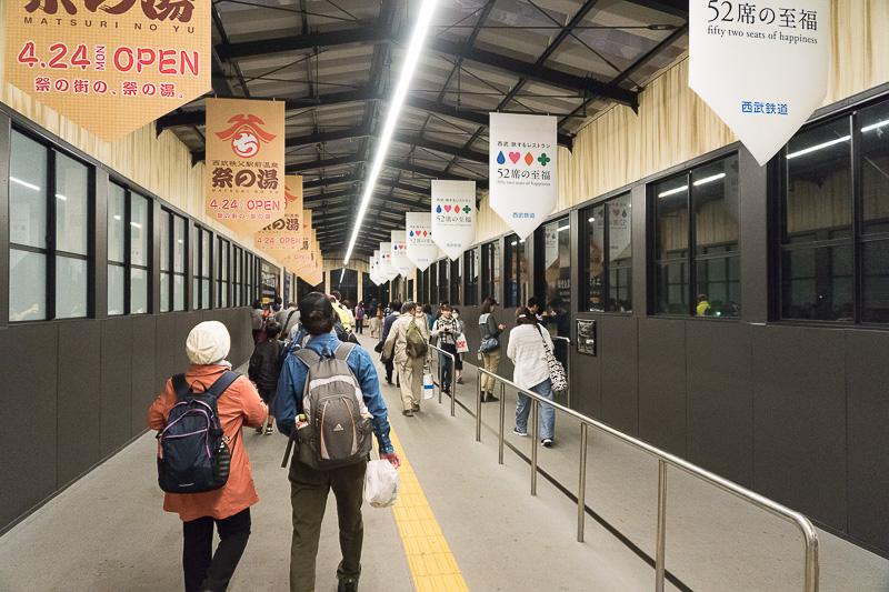 保線橋上を進む。4月に西武秩父駅前にオープンした「祭の湯」とレストラン列車「52席の至福」の広告