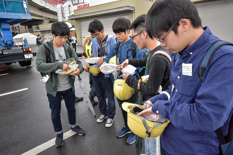 高所作業車に乗るということで、学生たちにヘルメットと安全帯が配布された