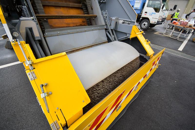 路面の清掃をする特殊清掃車。両脇のブラシは、路肩のゴミを掃き取る