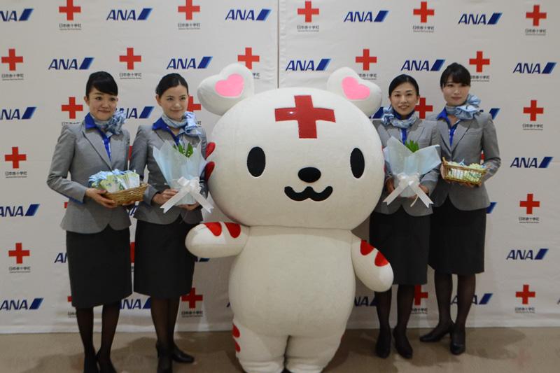 すずらんの贈呈を行なったCA(客室乗務員)と日本赤十字社のマスコットキャラクター「ハートラちゃん」