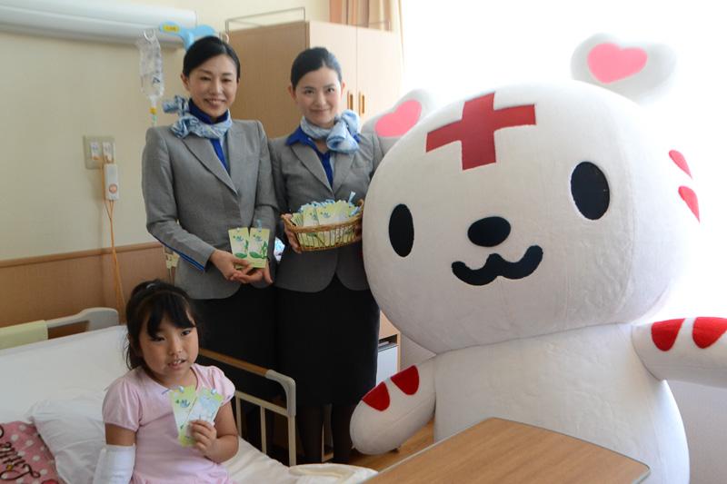 小児病棟の子供たちにすずらんのしおりを手渡したCAとハートラちゃん