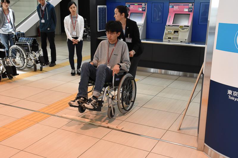 木の板を使って段差の乗り越え方を学ぶ。車椅子後部の突起を足で押して前輪を持ち上げる。このときも事前の声かけを忘れない