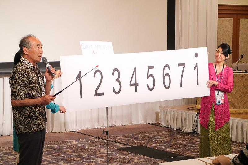 神戸インドネシア友の会 KISアンクルン代表の森井國興氏が、セミナー参加者にアンクルンの演奏を説明
