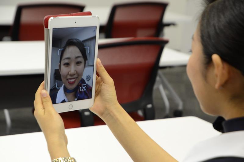 CAの岩嶋理乃氏。実際にアプリを体験、120%の笑顔を出してくれた
