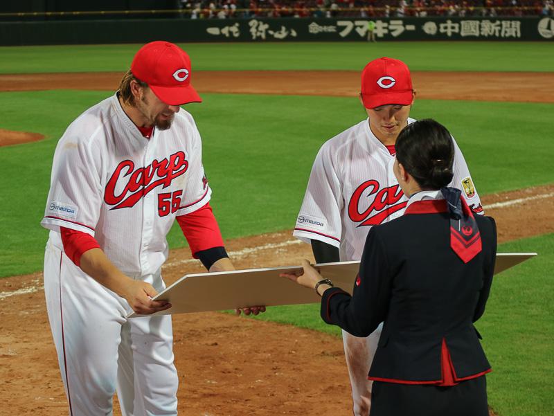 CAの河野里加子氏からブラッド・エルドレッド内野手と鈴木誠也外野手へ、MVP賞として「JAL国内線 往復航空券」が贈呈された