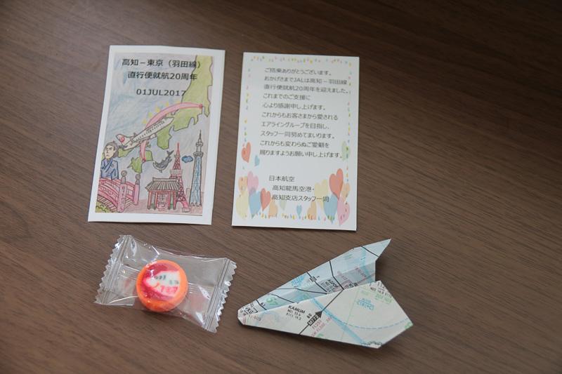 磯村康志支店長や歴代の制服を着用したJALスタッフらが、乗客に記念品を手渡していた。記念品はメッセージカード、アメ、航路図で折った紙飛行機