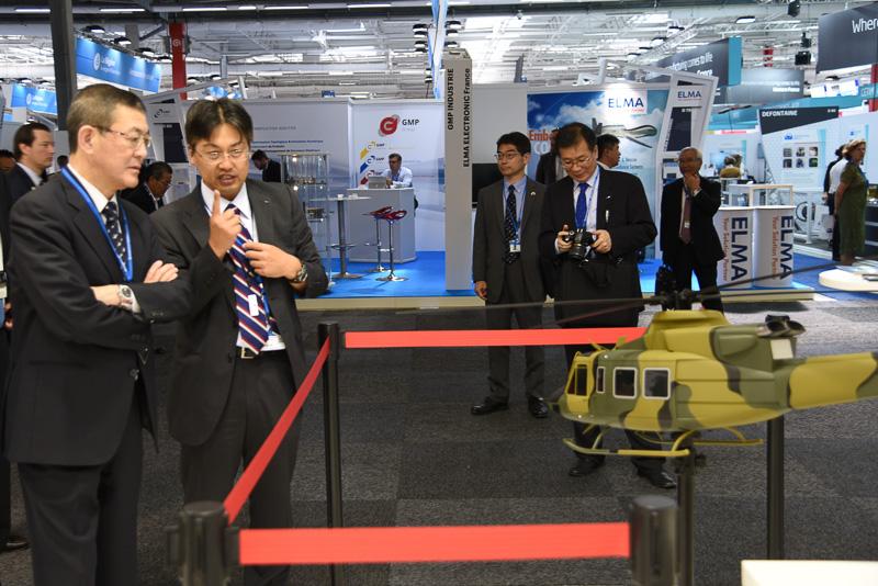 スバルブースで説明を聞くSJAC(日本航空宇宙工業会)会長 吉永泰之氏(左)