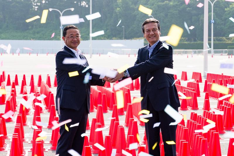 祝福のリボンが舞うなかで握手を交わすオリエンタルランド 上西社長とダイハツ 三井会長