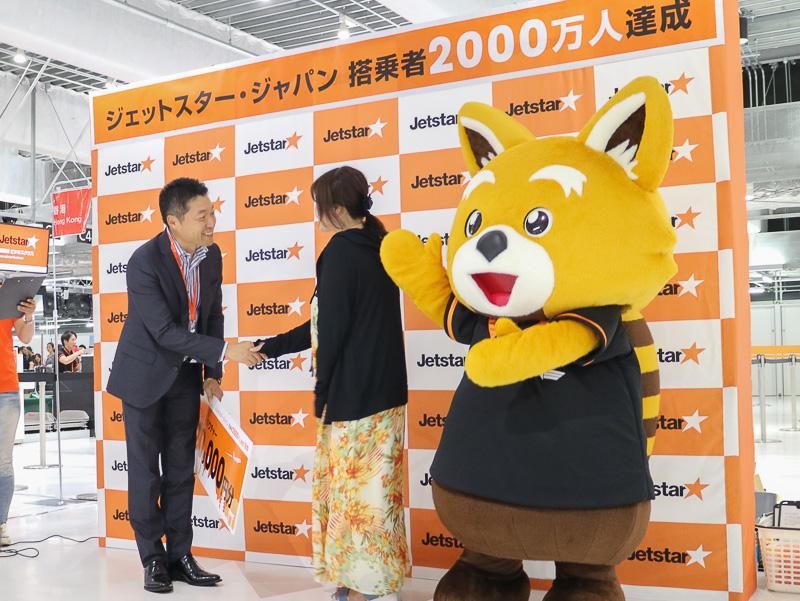 片岡優会長から松本彩さんへ、2万円分のフライトバウチャーが贈呈された