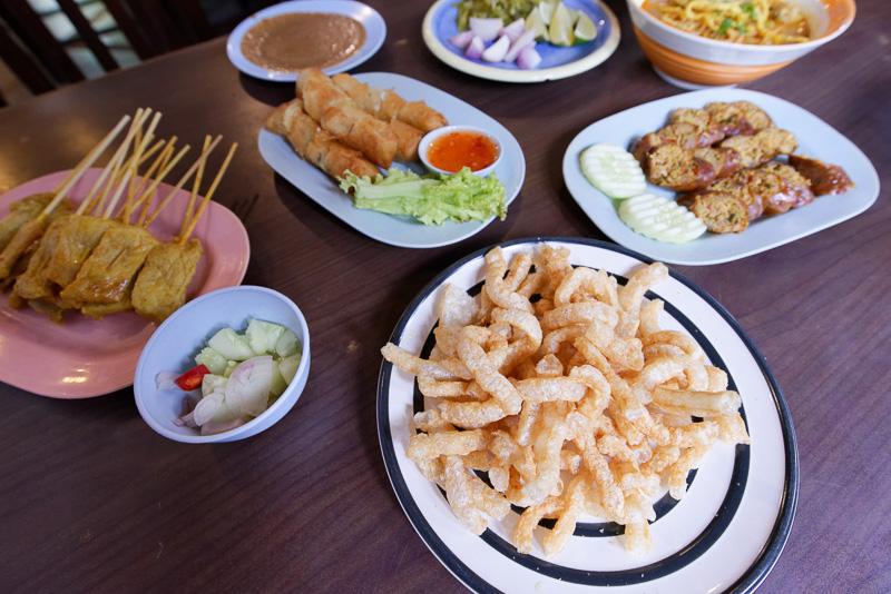 右下に見える揚げた豚皮や、その左に見えるタマネギなどをトッピングしたりする。左端は東南アジアでよく食べられる串焼き「サテー」