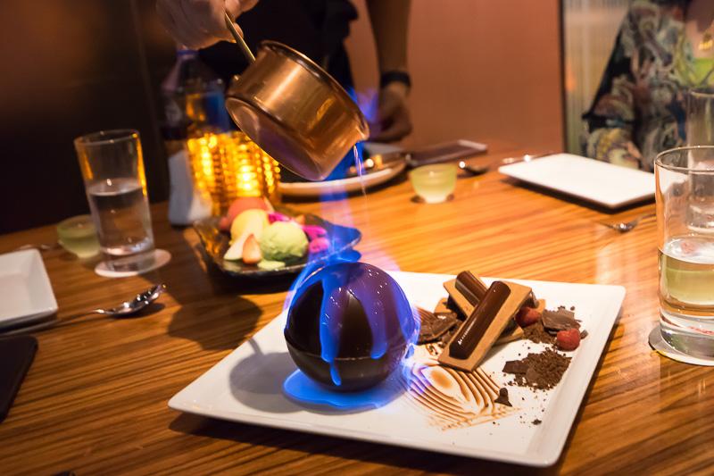 デザートのチョコトルテ。マシュマロの入ったボール型チョコにラム酒に火を付けかけている