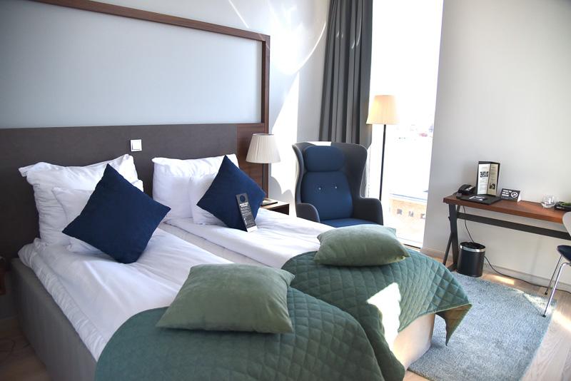 シックで落ち着いた客室。ツインベッドにはグリーンのベッドマットとクッション