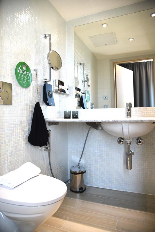 光の加減で色が変化する白いタイルを全面に使った清潔感あふれる洗面所とトイレ