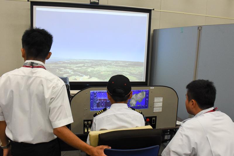 日本航空学園提供のフライトシミュレータの操縦体験。プロジェクタによる大画面で臨場感は抜群。指導官がつきっきりで離陸から着陸までアドバイスを送り、多くの子供がしっかり着陸していた