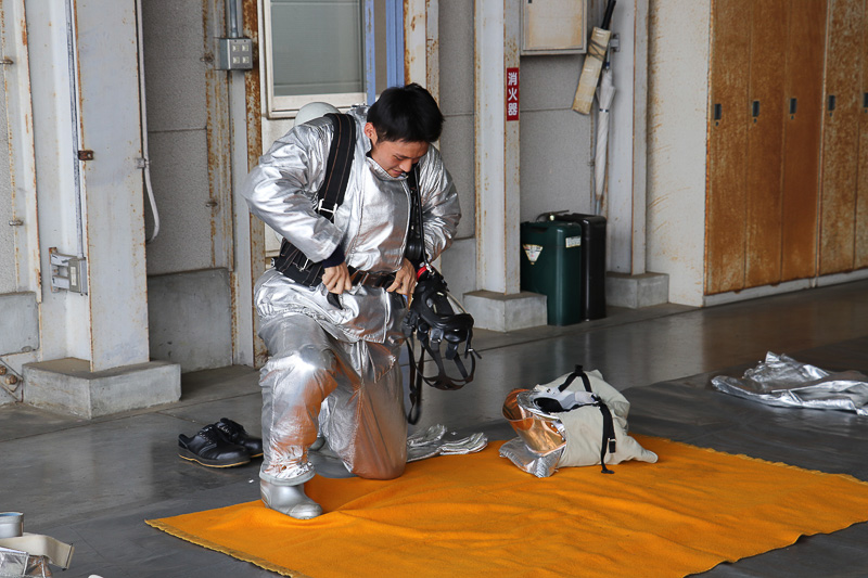 特殊な防護服を1分間で着る早業をデモンストレーション