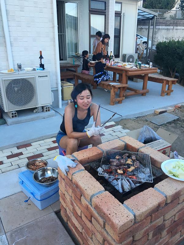 バーベキュー炉で肉を焼く大塚茉莉子さん