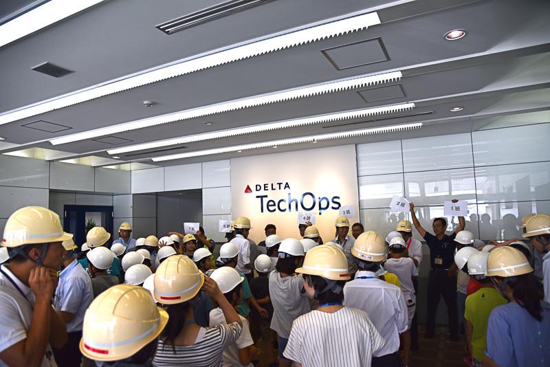 「デルタ・テックオプス(Delta TechOps)」のロゴ前で同社スタッフに挨拶