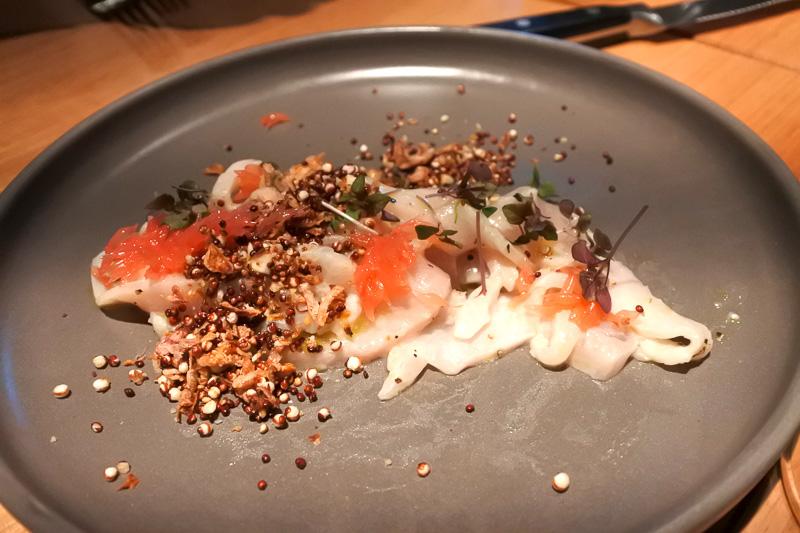 「sashimi of wild kingfish, bergamot dressing, grapefruit cells, cashew praline, puffed quinoa」