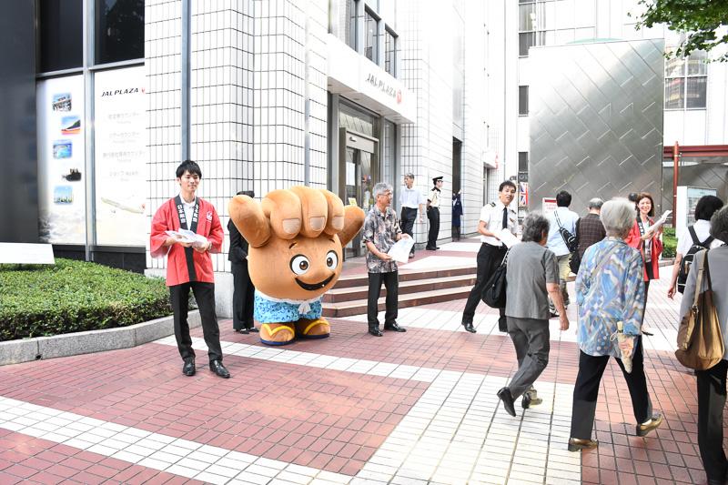 日本航空株式会社 代表取締役副社長 藤田直志氏(中央)も来店して、通行者にコナ線やジャルパックのパンフレットを配布した