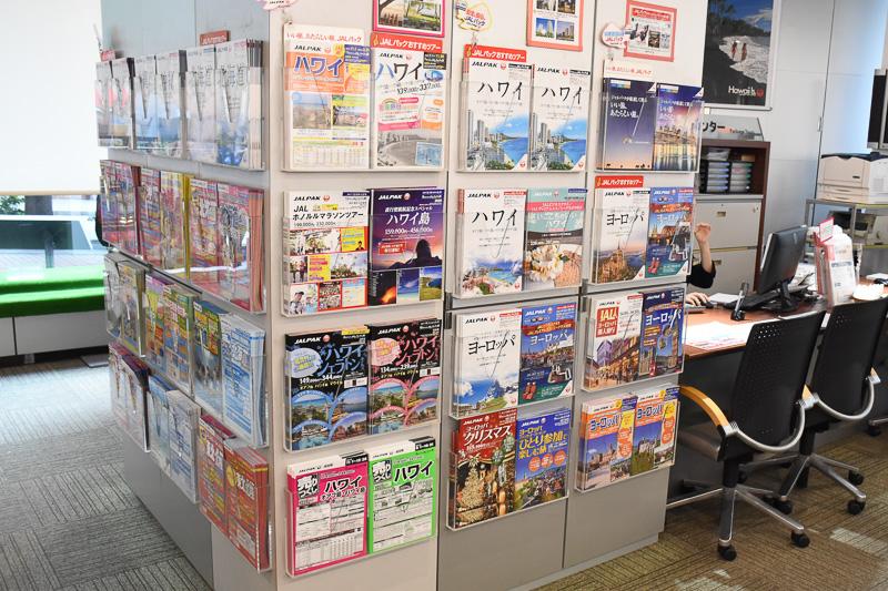 店内のラックに並ぶパンフレット。海外商品の売り上げ約4割はハワイ関連とのこと