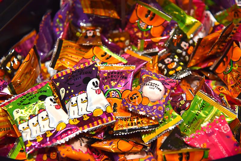 こんもりと盛られたお菓子たち。華やかなパッケージには、ゴーストに扮してお菓子を貰いにいく準備万端のミッキーマウスたちなどが描かれている
