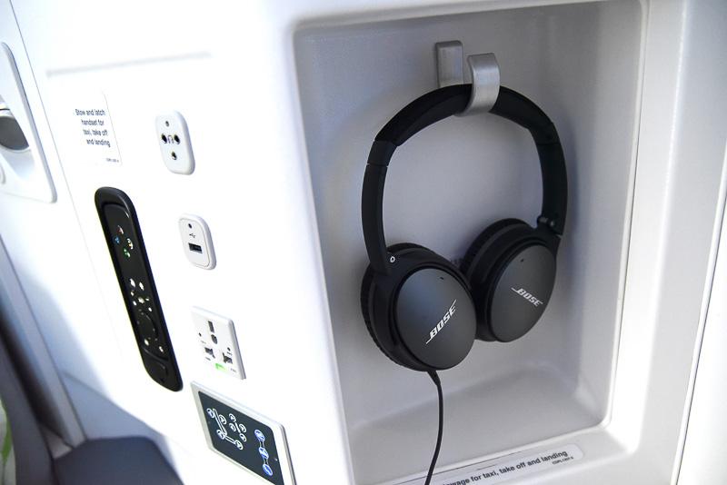 操作パネルには、モニター用のリモコンやリクライニングのボタン、ユニバーサルAC電源やUSBポートなどを集約。ボーズ製のノイズキャンセリングヘッドフォンを収納するスペースもある