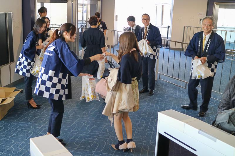 羽田空港 第1ターミナル19番ゲートにおいて、新千歳(札幌)行きSKY711便の搭乗客にスカイマーク株式会社 代表取締役社長の市江正彦氏や、同社スタッフが搭乗客にプレゼントを手渡した