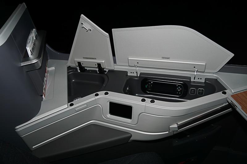 シート横にはアメニティキットを入れておいたり、電源などが用意されている蓋が用意されている。跳ね上げると隣との壁としても利用できる