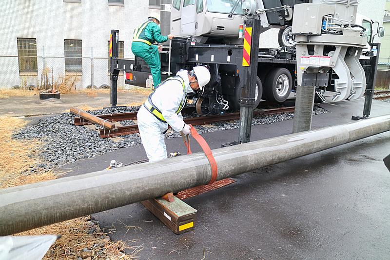 電柱をアームでつかんだら補助金具を作業員が取り付ける