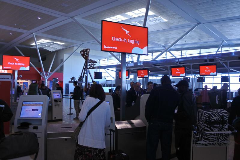 カンタス航空の自動チェックイン機で座席指定や荷物のタグ、搭乗券を発行。荷物はタグを付けたあとにカウンターで預け入れ