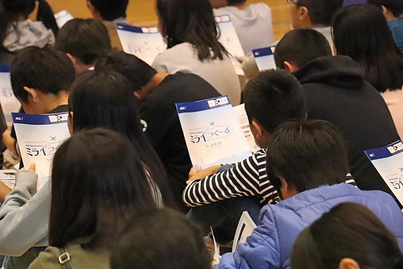 """生徒たちはワークブックの表紙に書かれた""""あんしん、あったか、あかるく元気!""""を確認"""
