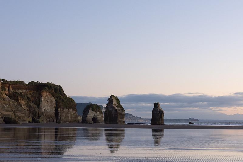 スリー・シスターズ・アンド・エレファント……だった岩たち。写真中央に立つ2つの岩が姉妹。その右の水面に少しだけ顔を見せている小さな岩が姉妹の3人目。そして、左側にある中央がくり抜かれた岩が象の形をしていた岩で、頭部が崩れて足だけが残っている